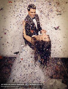 wedding photo of groom dipping bride with confetti falling