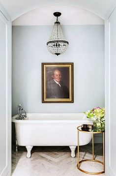 Serne blue bathroom corner with crystal chandelier and portrait