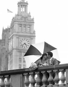 RAIN. A little rain can't ruin the day for this wedding couple! Make the umbrella a part of your shot. Beautiful black and white wedding photo with Chicago's Wrigley Building in background. Steve Matte. Wedding Photographer Chicago. Wedding photos; wedding photography; wedding photo ideas; Chicago wedding photography locations; Chicago wedding photo location ideas. #WeddingPhotos #WeddingPhotography