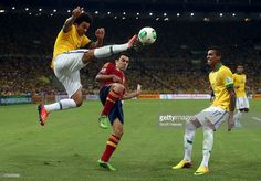Marcelo of Brazil beats Xavi Hernandez of Spain to the ball during the FIFA Confederations Cup Brazil 2013 Final match between Brazil and Spain at Maracana on June 30, 2013 in Rio de Janeiro, Brazil.