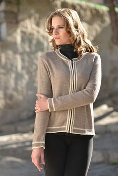 "This rolled classic features traditional cardigan styling with contemporary upgrades of zippered closure and soft rolled cuffs/ trims.  Modern texture shows its ""purl"" side out; all framed in simple graphic 2-tone trimming in Oatmeal and Ivory.  Light yet warm and supple, this 100% Baby Alpaca piece is sure to be a staple in every woman's wardrobe."