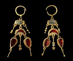A pair of Parthian gold and garnet earrings  Iran, circa 1st-2nd Century A.D. Each composed of gold loop hinged to a ovoid bezel below inlaid with green glass, from which a crescent shaped garnet-inlaid element is suspended, flanked by two gold bead strung wires, two pendant garnet inlaid teardrops hanging either side of a gold filigree bead strung wire, one with a small malachite bead, 2½in (6.3cm) long