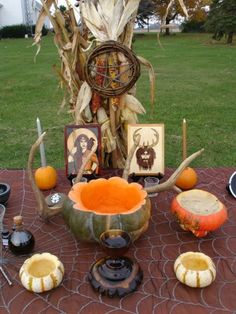Wiccan Samhain altar. All the hollowed out mini gourds used as candles and a cauldron are super cute. The spiderweb tablecloth is just the right touch of Halloween fun, too.