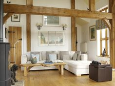 Crisp white upholstery and walls in this double-height living room are softened with raw wood furniture and plenty of natural light Raw Wood Furniture, Border Oak, Oak Framed Buildings, Oak Frame House, Self Build Houses, Modern Colonial, Live In Style, Buy Bed, Finding A House