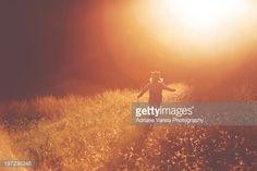 Little boy running in a field, sunset, wearing crown.