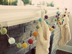 white knit stockings and felted pom pom garland makes a cute crafty holiday fireplace decoration. Noel Christmas, Winter Christmas, Handmade Christmas, Xmas, Whimsical Christmas, Christmas Things, Modern Christmas, Simple Christmas, Christmas Wedding