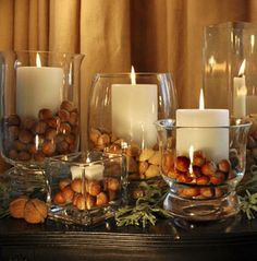 Thanksgiving decorating with acorns, large glass candle holders, and white pillar candles. Did you guys know that you need to either bake your acorns or put them in a freezer for a day before you put them out on display? Apparently there's a type of worm that likes to live in acorns and they can crawl out of your display! #ew #goodtoknow #lifehack