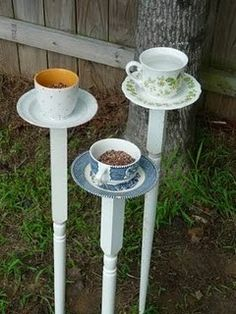 Tea cups and saucers on bed posts for birdseed.
