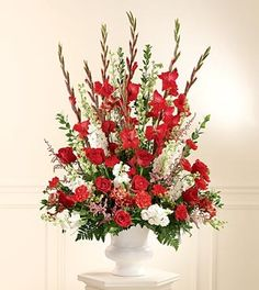 A traditional altar piece, this arrangement of red carnations, red roses, white stock and larkspur with pink astilbe in a white plastic urn is perfect for their wedding ceremony. Approx. 46H x 32W You