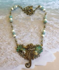 I used a B'sue seahorse for my focal pieces on this necklaces .. clam shells, pearls, rhinestones, sea shell, necklace blank and a filigree stamping were also used .. chain has pearls & jade with brass chain .. Jann Tague .. Clever Designs