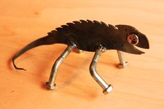 This happy little chameleon has bolt legs, and rivet eyes. Made from scrap metal.
