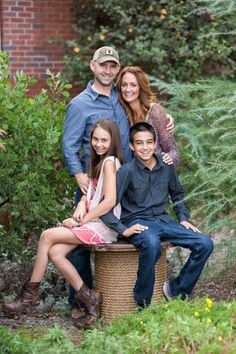 A photo of a family with a forest background, wearing blue ...