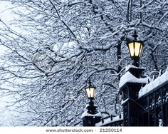 Antique street lamps on iron-wrought fence in the snow