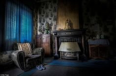 Forlorn: A pair of shoes sit in front of an empty armchair and ornaments remain above the fireplace in this abandoned home Niki Feijen