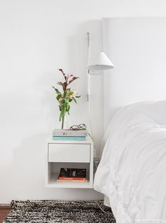 Quarto de casal neutro conta com luminárias de parede para otimizar o espaço disponível no criado mudo.
