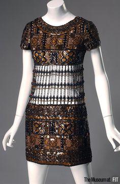 Evening dress Designer: Yves Saint Laurent 1936-2008  Medium: Brown organza, plastic plaques, bronzetone beads, black seed beads, and gold metallic beads Date: 1967