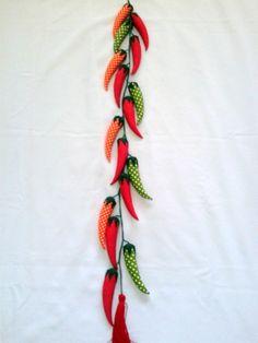 Móbile de pimentas em tecido 100% algodão. Enchimento fibra siliconada. Cordão sintético. Acabamentos em feltro verde. Contém 16 pimentas distribuídas no fio do móbile. e um pompom no final. Este móbile é usado na decoração da cozinha, na cortina ou atrás da porta. A medida é da argola ao pompom. Cada pimenta mede 14cm de altura por 04 cm de largura medindo no meio da pimenta. O Móbile completo mede 125cm CONSULTAR DISPONIBILIDADE DE ESTAMPAS ANTES DE EFETUAR O PAGAMENTO