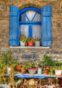 Cretan window .... very Greek with the blue shutters and potted plants....