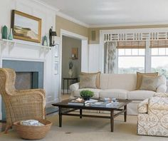 living room with wicker wingback chair, fireplace, white rolled arm sofa, coffee table and sisal rug.