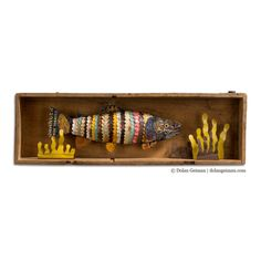 Trout in Wooden Box Faux Taxidermy Fish Diorama by Dolan Geiman. 3-D wall sculpture features a colorful trout fish constructed from hand-cut salvaged metal swimming beside underwater vegetation inside an old wooden box. #outdoors #fisherman #masculine