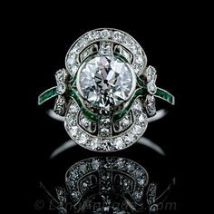 This absolutely exquisite Edwardian diamond ring features a 1.80 carat sparkling European cut diamond set in a semi-bezel surrounded by small accent diamonds and calibre cut emeralds with adorable bow motif shoulders. Pristine Condition.