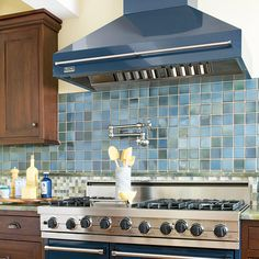 Break up an oversize blue backsplash by pairing a panel of large glass mosaic tiles in navy hues with smaller tiles that incorporate white. The medley of colors keeps the kitchen comfortable yet cohesive. Kitchen Vent, Kitchen Cabinetry, Kitchen Backsplash, Kitchen And Bath, New Kitchen, Kitchen Dining, Kitchen Ideas, Kitchen Hoods, Kitchen Designs