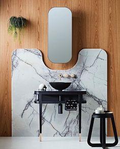 Aplicado na parede como um sinuoso painel, o mármore contrastou com o tom quente da madeira e ganhou ainda mais destaque no espaço!