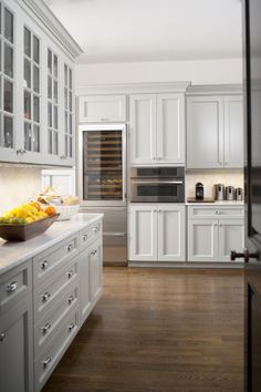 white-painted poplar cabinets are inset for a quality look and feel. Topping them is Calacatta Gold Marble, which also graces the backsplash in solid slabs.