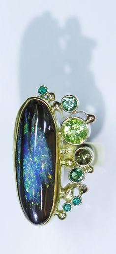 Boulder opal (opalized wood) ring with tsavorite garnet in 22k and 18k gold.  Opal from Bill Kasso