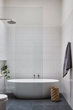 In this modern master bathroom, simple rectangular white tiles have been installed vertically, while Signorino stone tiles cover the floor. White Bathroom Tiles, Modern Master Bathroom, Family Bathroom, Bathroom Renos, White Tiles, Remodel Bathroom, Bathroom Ideas, Bathroom Shower Tiles, Black And White Master Bathroom