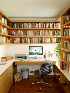 Neat office surrounded by bookshelves with subtle led lighting underneath the shelves.