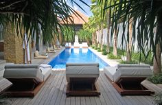 A sun deck wraps around two sides of the 15-metre pool, furnished with loungers and outdoor cushions.