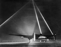 An Avro Lancaster on the runway before taking off for an air raid, with searchlights indicating the height of the cloud base, 1943