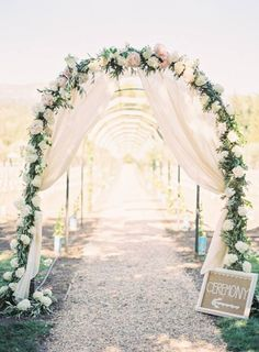 An archway covered with blooms and greenery with sheer draping welcome guests to an outdoor ceremony ~ http://www.stylemepretty.com/california-weddings/2016/04/18/family-florals-make-this-napa-valley-wedding-a-winner/