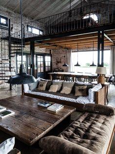 Living comedor de gran altura en una casa de campo con entrepiso para juegos. Mesa baja de tablones de madera, grandes sillones, lámparas galponeras y paredes de ladrillo.