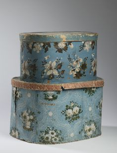 TWO FLORAL PATTERN WALL-PAPER COVERED BOXES WITH BLUE GROUND INCLUDING A WOODEN EXAMPLE.  Height of largest 12 inches, l...