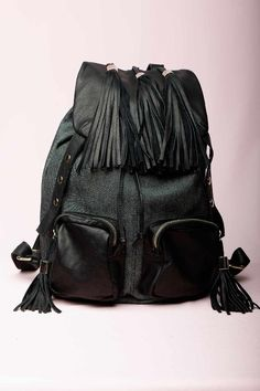https://www.cityblis.com/6008/item/15517  JEFFREY CAMPBELL TRIO BLACK LEATHER BAG - $279 by Jeffrey Campbell  Girls We Hated In High School Handbags by Jeffrey Campbell >3 Girls     Canvas & leather backpack, drawstring top and fold-over flap embellished with over-sized tassels, 2 front zip pockets with tassel fringe zipper pulls.  Lining with interior zip pocket, magnetic closure on exterior flap.