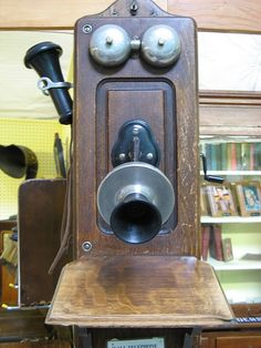 Antique Telephone. Had this model in our one horse town in Canada. Everyone is on a party line and you're not supposed to answer unless you hear your special ring, maybe a long short short or whatever. My mom never listened in on anyone, she wouldn't do that.