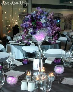 One of eight mixed purple floral centrepieces with martini vases and LED lights, created and set up for a couple, their wedding reception was held in at Tropical North Queensland Musuem in Townsville.