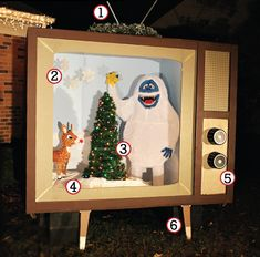Amazing outdoor Christmas decoration: A giant retro TV with a scene from Rudolph the Red Nosed Reindeer-- Made from stuff you can buy at Home Depot. #Christmas #DIY