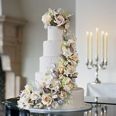 WOW Brides: Wedding Cake with Orchids and Roses. This five-tiered cake is the perfect finale. It's embellished with lace appliqu� icing and a cascade of sugar flowers, roses in five stages of bloom, cattleya orchids, sweet pea, lilies of the valley, and morning glories.