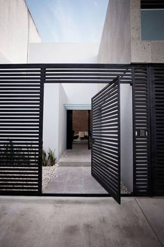 This modern screen provides a nice partition between the entrance way, courtyard and street. Sloped Yard, Raised Garden Beds, Landscape Architecture, Fence, Garage Doors, Sloped Backyard, Composite Fencing, Sloped Front Yard, Landscape Architecture Design