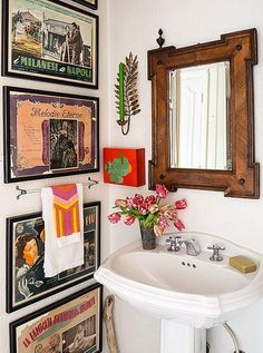 Vintage Italian movie posters line a bathroom wall. The all-white background gives a nook like this an organizing structure, which lets Lulu play around with fun pops of color.