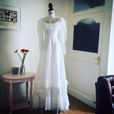 """Our beautiful """"aurora"""" 1970's wedding dress featuring stunning lace detail. Falling slightly longer at the back and boasting a high neck, the """"aurora"""" has an ethereal feel to it making it perfect for summer weddings. The dress is in extremely good vintage condition but there has been a slight tear on the very bottom hemline. (See photo) We hope you love """"aurora"""" as much as we do! Let your dress go down i..."""