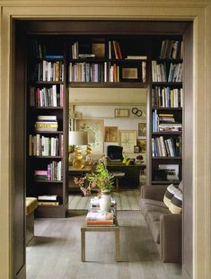 Mark Lee and Ed Filipowski at Home in Manhattan; Architectural Digest - Bookshelves by Janson Goldstein in the library frame a view of the living room. The Italian cocktail table from Mondo Cane, stained European oak flooring. Bookshelves Built In, Interior Design, House Interior, Home Library, Home, Interior, Couples Apartment, New York Apartment, Home Decor