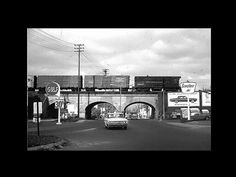 Piqua, OH triple arch train bridge over College Street. The Miami Erie Canal ran along this route until much of the canal line was severely damaged by the 1913 Great Miami River flood. Photo credit unknown circa late 1960s. Gulf and Sinclair gas stations. Price of gas was 30.9.