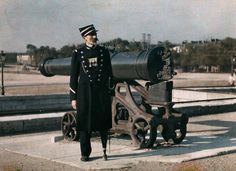 An invalid soldier stands beside a cannon in Paris, 1923. Photograph by Jules Gervais Courtellemont, National Geographic