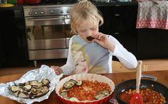 Jobke is druk bezig om de ovenschaal te vullen met aubergine en tomatensaus voor de stoofpot van aubergine, tomaat en kikkererwt. Recept is van Martha Rose Shulman.