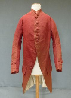 Coat and breeches, England, 1760s. Red coloured vertically narrow striped cut and uncut velvet, a minute repeat pattern alternating with a plain stripe, large covered buttons, ivory silk lining. Breeches with fall front held by two covered buttons.