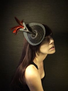 Dark Grey Felt Cocktail Hat with Black Leather, Orange Feathers, and Vintage Button Accents. $78.00, via Etsy.